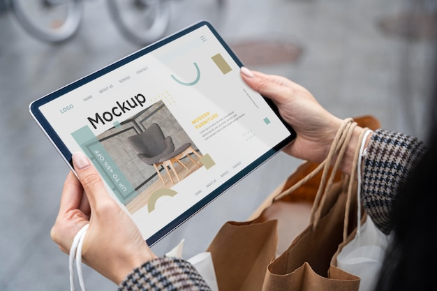 High angle woman with shopping bags holding tablet mock-up Premium Psd