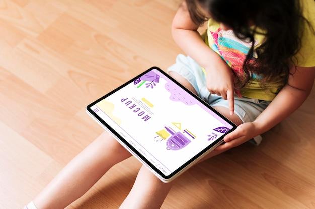태블릿 디지털 모형을 사용하여 높은보기 소녀 프리미엄 PSD 파일