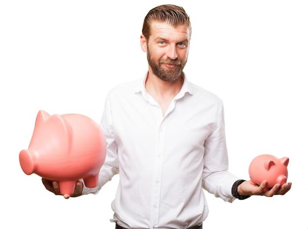 Hombre de negocios que sostiene dos huchas de diferentes tamaños Free Psd