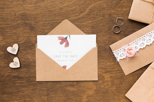 招待状のモックアップと木製の背景の結婚指輪 無料 Psd