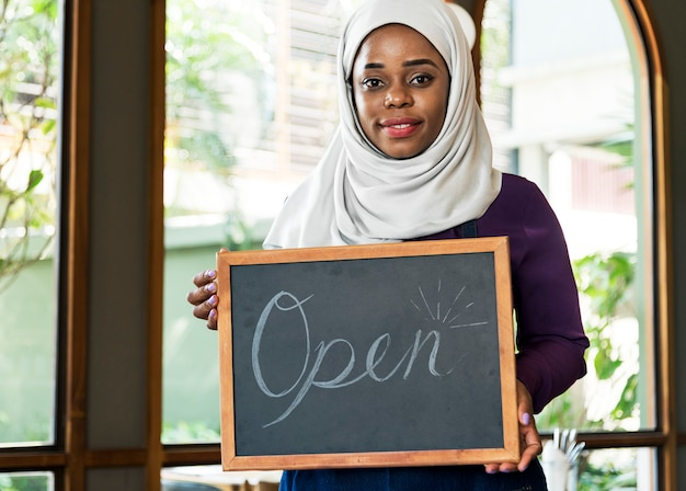 Islamic woman small business owner holding blackboard with smiling Free Psd