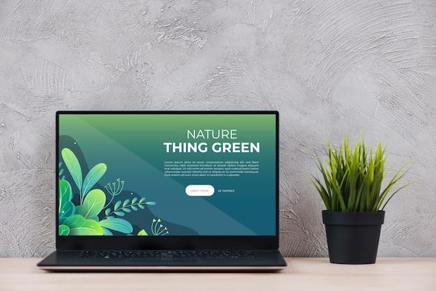 Laptop beside plant on desk at office Premium Psd