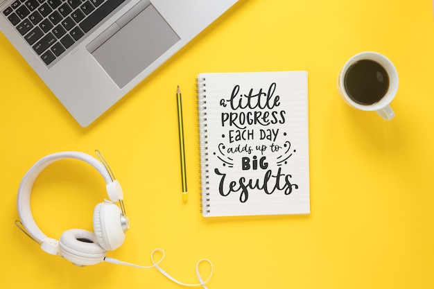 Laptop coffee headphones and notebook on yellow background Free Psd