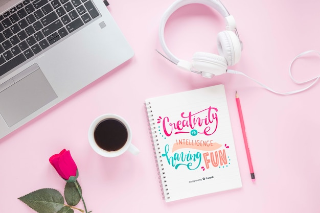 Laptop headphone and notebook on pink background Free Psd