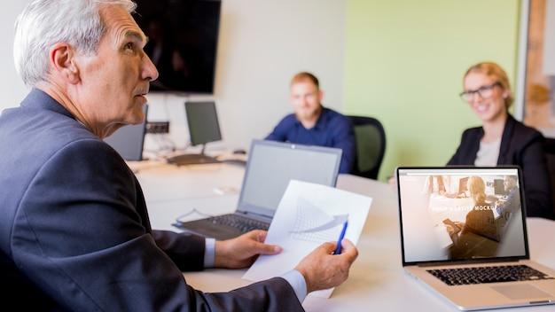 Laptop mockup at business meeting Free Psd