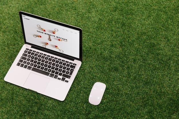 Laptop mockup on grass Free Psd