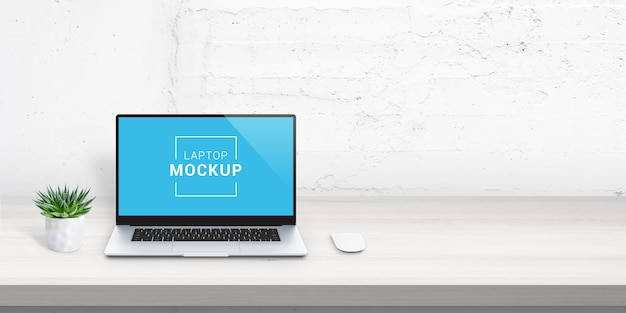 Laptop mockup on office desk with free space beside for promo text. plant and mouse beside. white brick wall in background. scene creator with isolated layers Premium Psd