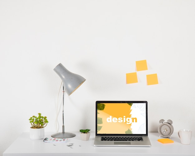 Laptop mockup on desk with elements Free Psd