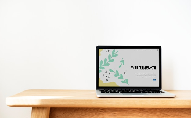Laptop showing website template on a wooden table Free Psd