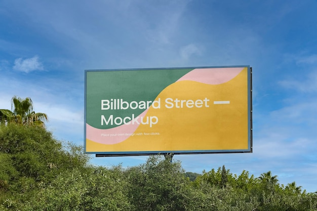 Large billboard mockup on blue sky with trees Free Psd