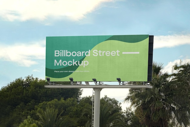 Large billboard mockup with palm trees Free Psd