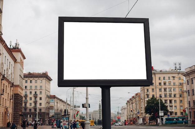 A large billboard with interesting information and advertising on it installed along a wide street in the city center Free Psd