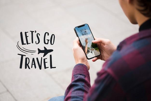 Давайте отправимся в путешествие, и человек смотрит на свой телефон через плечо выстрел Premium Psd
