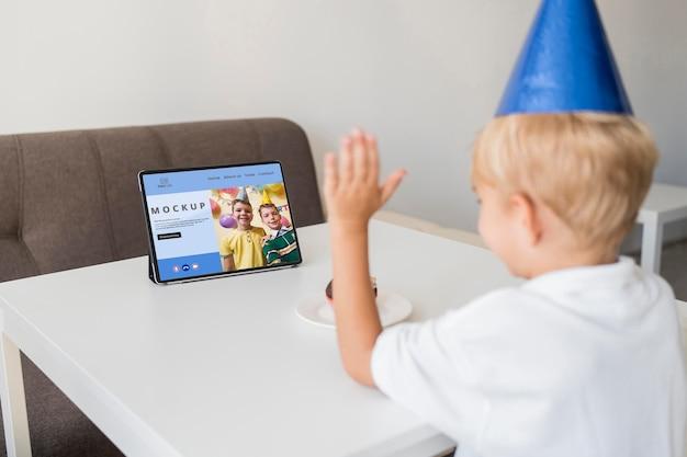 タブレットで家で祝う小さな男の子 Premium Psd