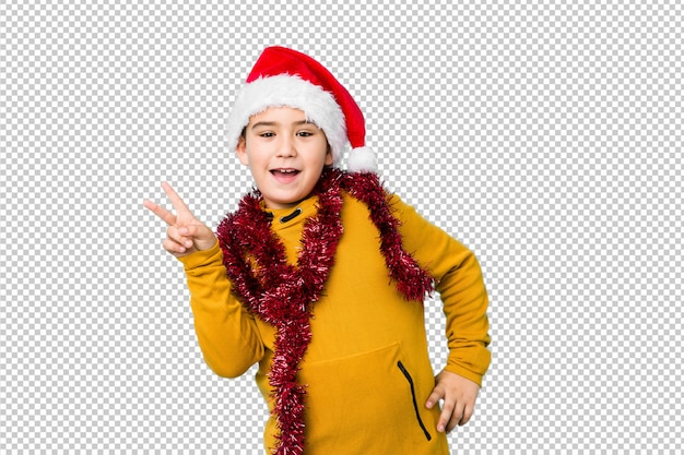 Мальчик празднуя рождество нося шляпу santa изолировал радостный и беспечальный показывать символ мира с пальцами. Premium Psd