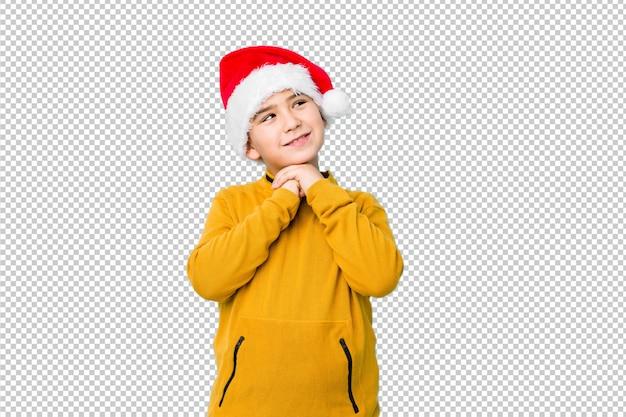 Мальчик празднуя рождество нося шляпу santa держит руки под подбородком, смотрит счастливо в сторону. Premium Psd