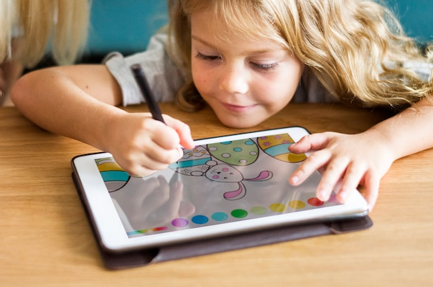 Little girl coloring on a tablet Premium Psd