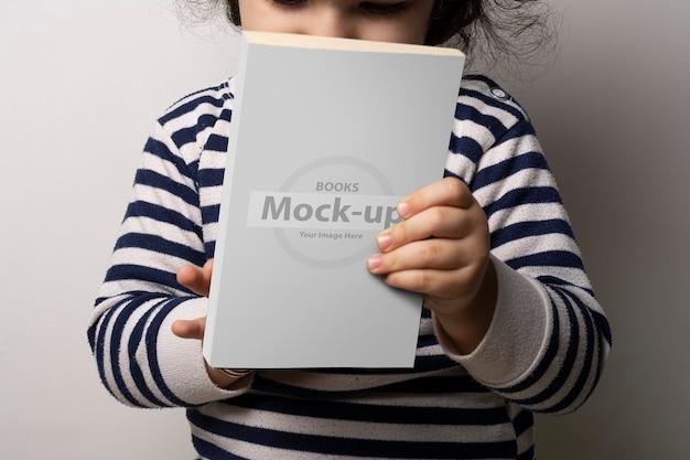 体のモックアップの前にブランクカバーの小説本を保持している少女 Premium Psd