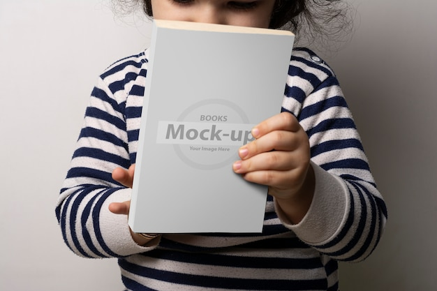Little girl holding a novel book with blank cover in front of body mock-up Premium Psd