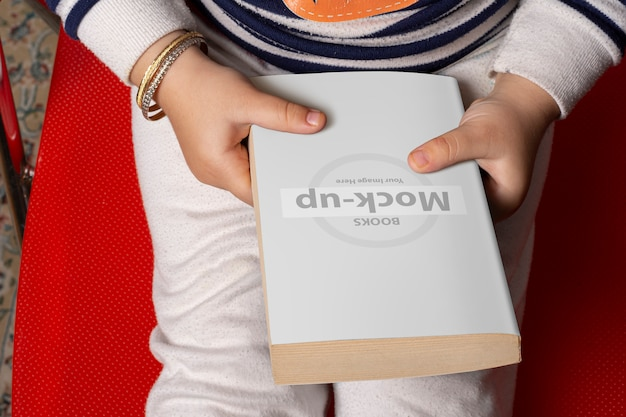Little girl holding a novel book with blank cover in front of body Premium Psd