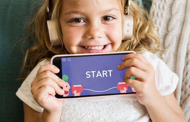 Little girl playing a mobile game Premium Psd