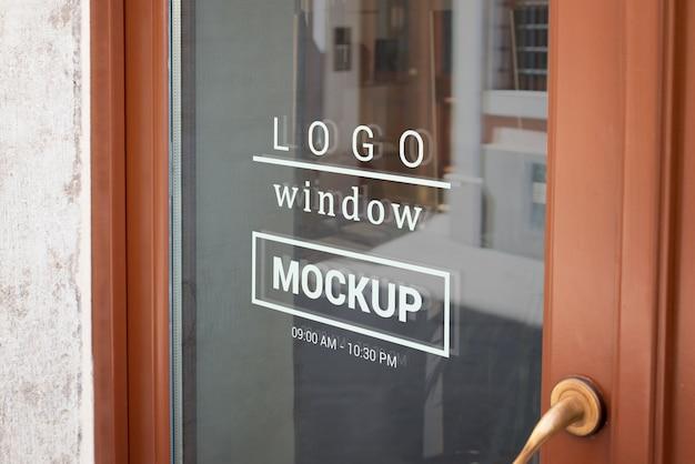 店の正面玄関の窓にロゴのモックアップ Premium Psd