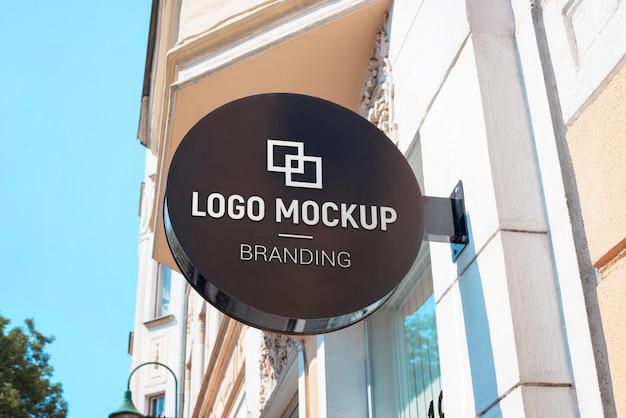 Logo mockup on round street sign above the store. modern, black signage Premium Psd