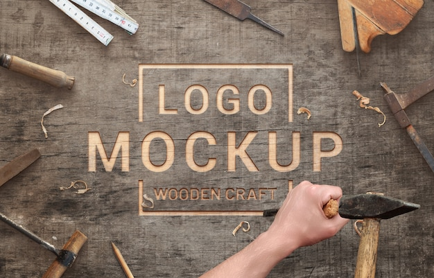 Logo mockup on wooden surface scene creator. carving with chisel and hammer concept. Premium Psd