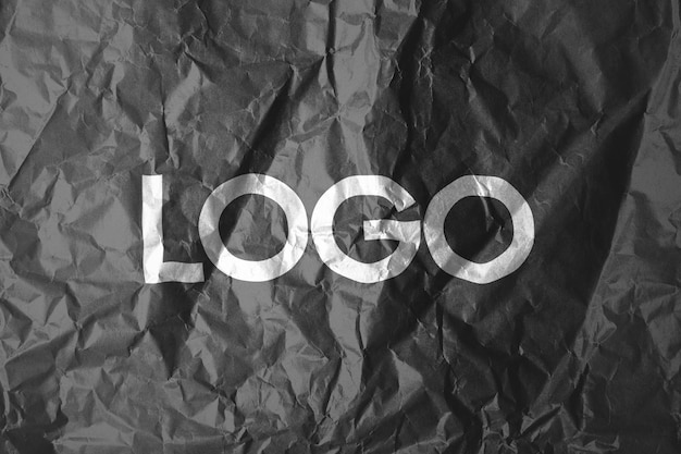 Logo template on crumpled paper Free Psd