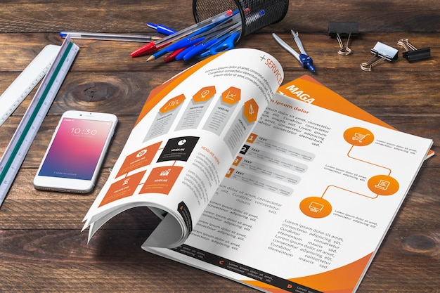 Magazine and smartphone mockup on wooden table with pens and rulers Free Psd