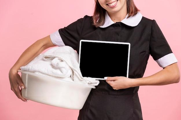 Cameriera con asciugamano tenendo il tablet mock-up Psd Gratuite