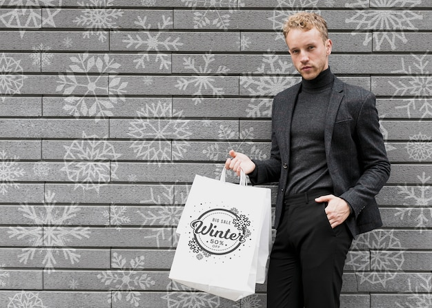 Male in black suit with shopping bags Free Psd