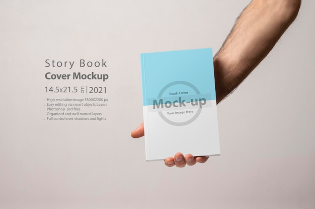 Male hand holding a closed book-catalog with blank cover mockup