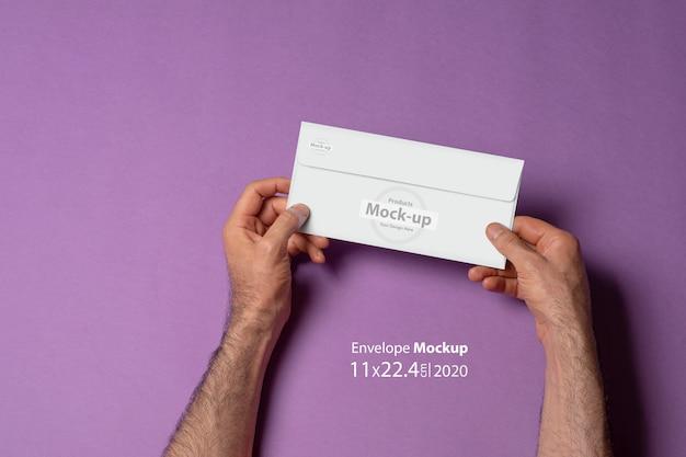 Male hand holding a letterhead paper envelope mock-up Premium Psd