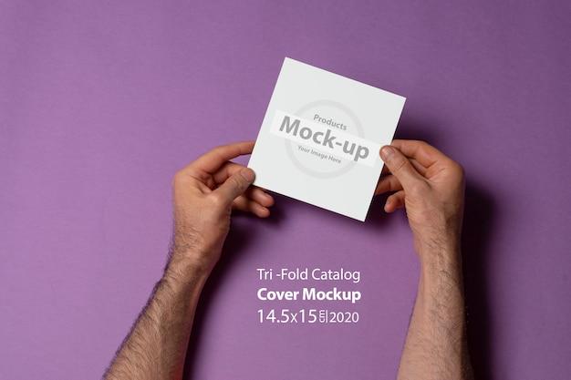보라색 표면에 빈 표지와 사각형 크기의 삼중 카탈로그를 들고 남성 손 프리미엄 PSD 파일