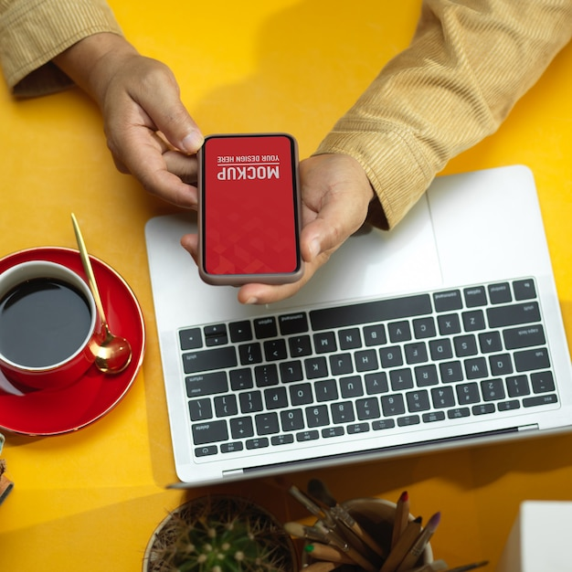 Male hands using smartphone mockup with laptop and coffee cup on the table Premium Psd