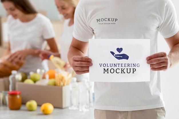 Мужчина-волонтер держит чистый лист бумаги с женщинами, готовящими коробки с пожертвованиями на еду Premium Psd