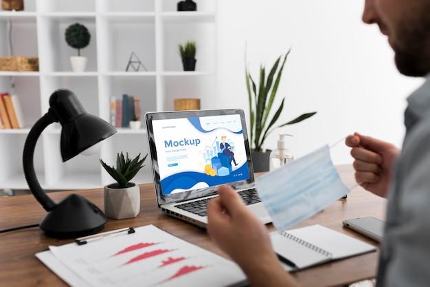 Человек за столом с маской и макетом ноутбука Бесплатные Psd