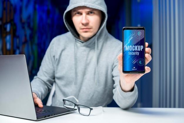 Человек за своим столом с макетом цифровой безопасности мобильного телефона Premium Psd