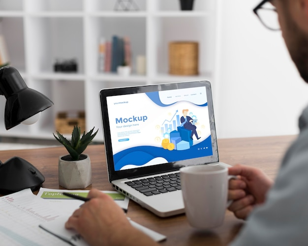 Man at desk with laptop mock-up Free Psd
