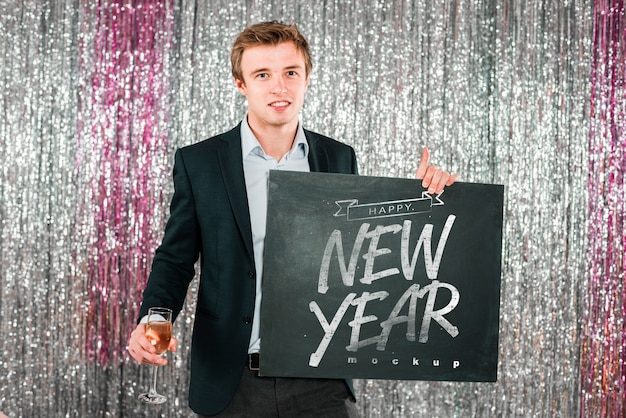 Man holding blackboard for new year Free Psd