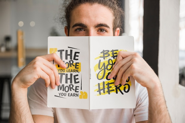 Man holding book cover mockup in front of face Free Psd