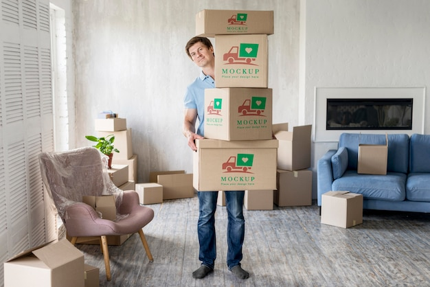 Man holding boxes with objects in his new house long view Free Psd