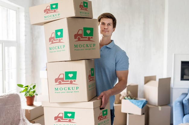 彼の新しい家でオブジェクトとボックスを保持している男 無料 Psd