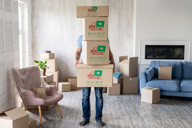 Man holding boxes with objects indoors Free Psd