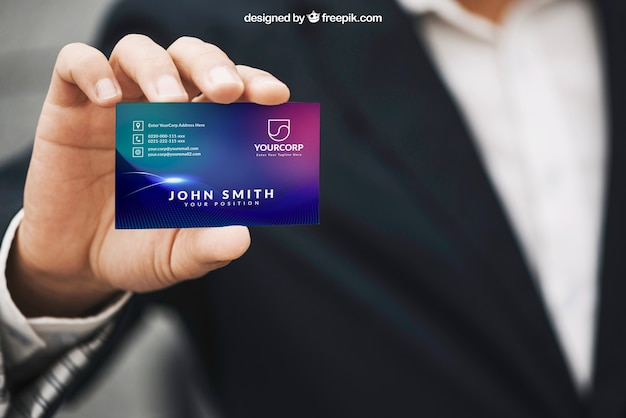 Man holding business card mockup Free Psd