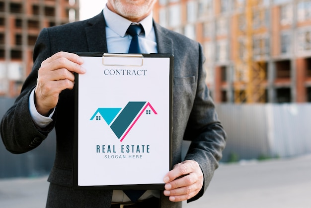 Man holding a clipboard mock-up for architectural business Free Psd