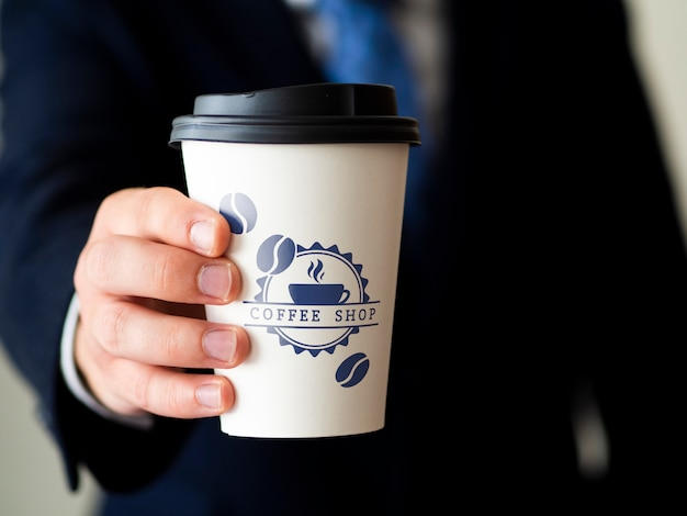 Man holding a coffee cup mock-up Free Psd