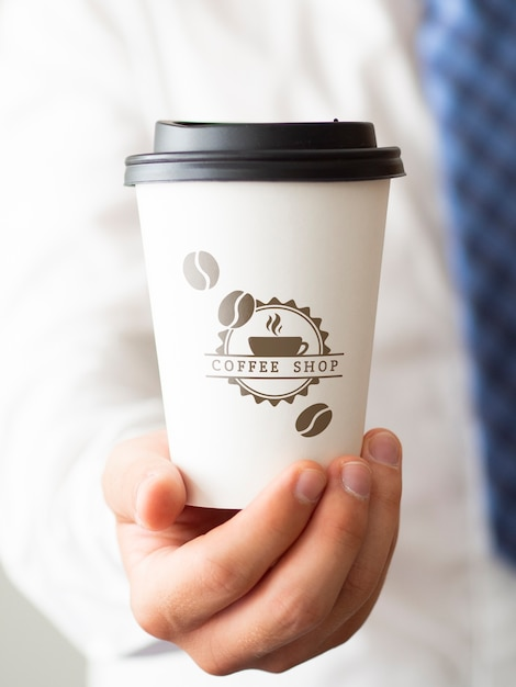 Man holding a cup of coffee close-up Free Psd