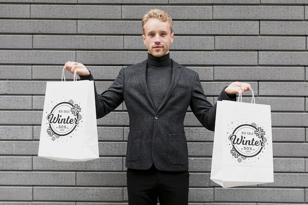 Man holding in each hand shopping bags Free Psd